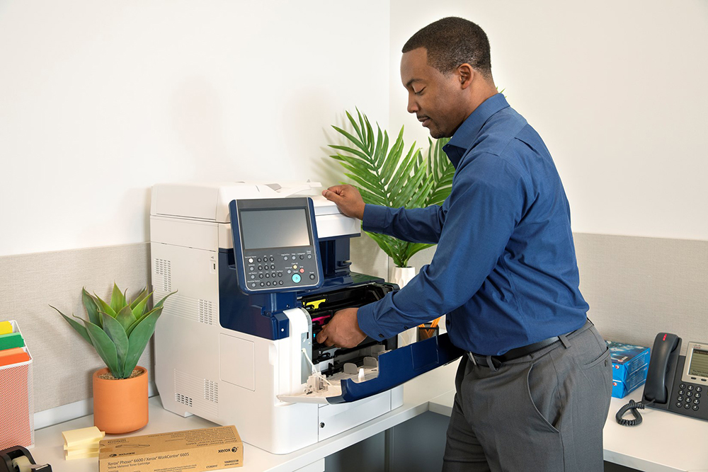 Man changing toner in printer