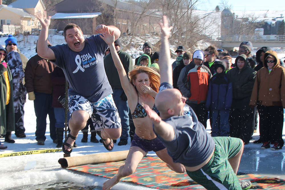 Rhyme employees leap into the water during the Lee Lake Polar Plunge